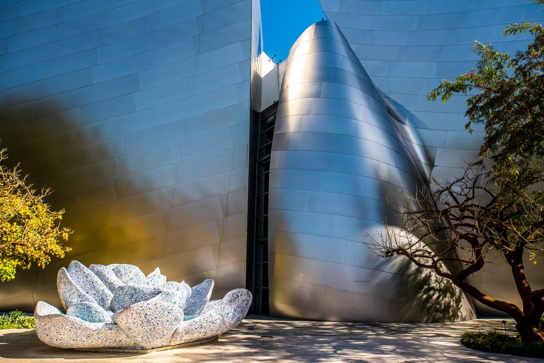 Часть изогнутого металлического фасада и каменный цветок