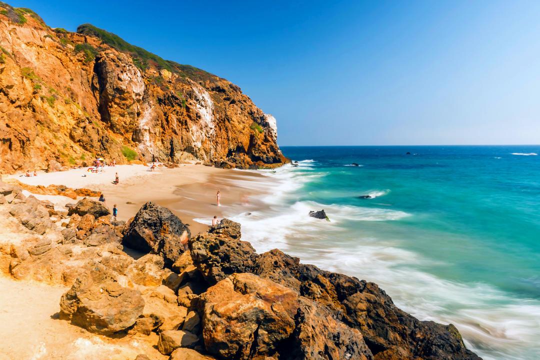 Изумрудно-голубая вода на тихом пляже в окружении скал
