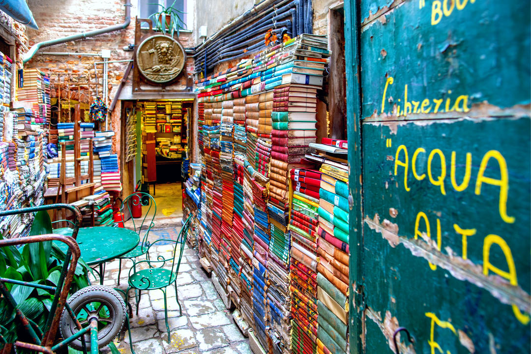 Стены из книг и зеленый столик со стульями
